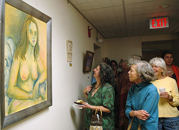"Attendees at the ""Women's Voices Out Loud,"" performance took in the controversial art exhibit in the John Bryan Community Gallery at intermission. In the foreground is local artist Deb Housh's painting, ""More Nudes Please."" After several Village employees who work in the John Bryan Community Center complained about nudity and sexual content in artwork at the annual exhibit, Council decided to develop a local public art policy."