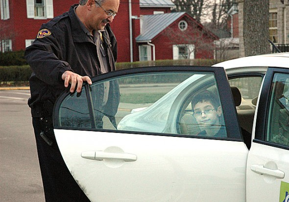 Yellow Springs Police Chief John Grote is retiring at the end of this month after 25 years with the department. He's shown here at his daily morning duty helping Mills Lawn School kids get out of cars and into the school safely. A reception for Chief Grote, plus two other Village retirees, will take place Thursday, March 29, at 11:30 a.m. in rooms A and B at the Bryan Center.