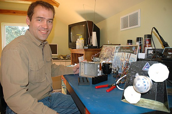 From his home office on Allen Street, local aerospace engineer Jake Freeman designs the instruments for life science experiments in outer space. In his work for BioServe, Freeman, a Yellow Springs High School graduate, has contributed to experiments that have led to new antibiotics and vaccines and added to an understanding of plant and animal behavior. Here Freeman tinkers with a container used in testing the behavior of Monarch buttlerflies in space. (Photo by Megan Bachman)