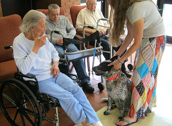 Kait and John Seyal brought their therapy dogs, Grace and Max, to the Friends Care Center last weekend to visit with residents, including, from left, Jeanette Wiggins, JoJo Campbell and Homer Williams. The couple is walking across the country with their dogs to promote dog therapy and animal rescue.