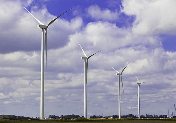 476-foot wind turbines spin over farms in northwest Ohio as part of the 152-turbine Blue Creek Wind Farm. The Village will decide this month whether to purchase electricity from the 304-megawatt wind project, located 100 miles north of the village. (Submitted photo courtesy of Ibedrola Renewables)