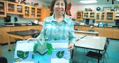 McKinney School seventh- and eighth-grade science teacher Terry Graham retires at the end of the school year to return to science field work and spend more time with family. Here Graham shows off a student project on the rainforest. During her 12 years at McKinney, Graham said she enjoyed encouraging student creativity and teamwork through projects. (Photo by Megan Bachman)