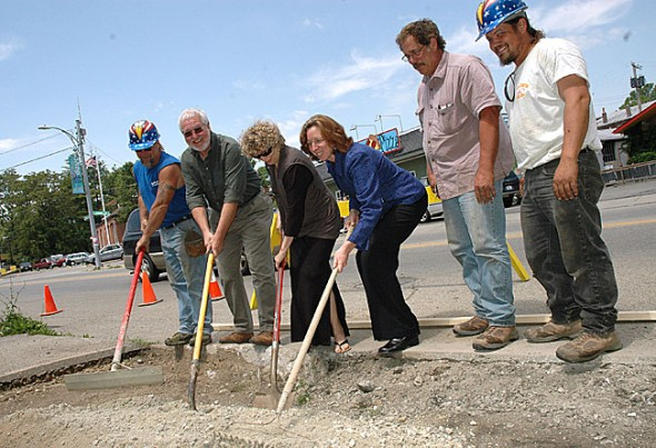 Village officals helped Lamont Excavating workers spread gravel at a sidewalk repair groundbreaking along Xenia Avenue downtown. From left are Guy LaPlante, Village Planner Ed Amrhein, Village Council member Karen Wintrow, Village Interim Manager Laura Curliss, John Lamont, owner of Lamont Excavating, and Erick Gohlke. (Photo by Megan Bachman)