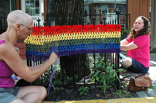 On Saturday, July 28, local residents Susan Gartner, left, and Theresa Mayer rehung a knitted sleeve that was removed last week without permission from one of the the trees downtown. (photo by Lauren Heaton)