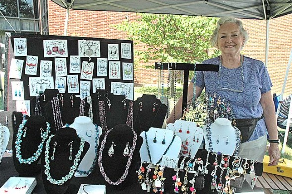 Villager Dinah Anderson, shown displaying her original jewelry, was one of several local artists selling their wares at the 2011 Art on the Lawn. This year's event, sponsored by the Village Artisans, will take place this Saturday, Aug. 11, from 10 a.m. to 5 p.m. on the lawn in front of Mills Lawn School. (photo by Diane Chiddister)