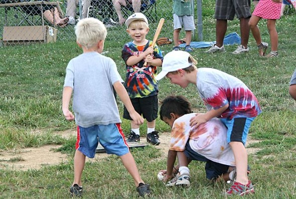 Kian Rainey, age 3, had a great time at Gaunt Park Friday night. Most of the time he ran around with several baseballs in his hands. Above, Rainey's successful turn at bat led to a mad scramble towards home plate by at least three decidedly shortstops. (photo by Suzanne Ehalt)