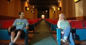 The Little Art Theatre is close to getting a complete renovation — the first in its 83-year history. Above, Little Art Executive Director Jenny Cowperthwaite and longtime 35-mm projectionist Andy Holyoke sit in the 37-year-old theater seats that will soon be replaced. (Photo by Megan Bachman)