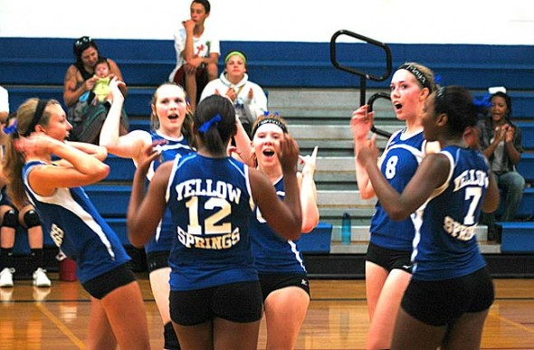 Members of the Yellow Springs High School girls varsity volleyball team celebrated after winning a point during a comeback victory over visiting Greenon in straight sets. The Lady Bulldogs started their season 3–0. (photo by Megan Bachman)