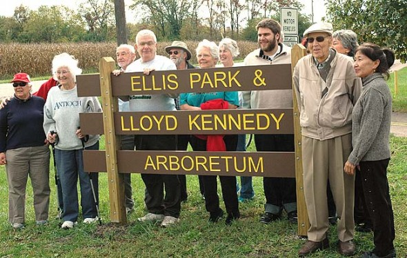Lloyd Kennedy, second from right, stood at the sign that bears his name during the rededication of Ellis Park, which has been renamed in honor of Kennedy and his long-term commitment to planting trees in the village. (Photo by Lauren Heaton)