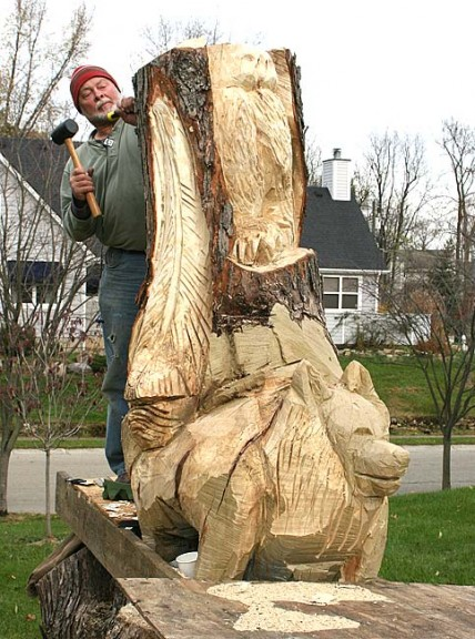 Mural artist and sculptor Greg Ackers is about 40 hours into a rendering of snow owls, a dog and feathers from a massive tree stump. (Photo by Suzanne Ehalt)