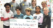 The fourth-grade class at Mills Lawn school proudly presented a check to the Yellow Springs Food Bank this week for $182.92. (Photo by Lauren Heaton)