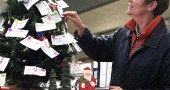The annual Share the Joy holiday gift-giving tree is going up soon at the YS Community Library. Pictured is Debbie Henderson, tending the 2012 Share the Joy tree. (Photo by Jeff Simons)