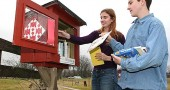On Sunday Regina Brecha and Max Mullin restocked the Mullin family's Little Free Library on State Route 370. (Photo by Suzanne Ehalt)