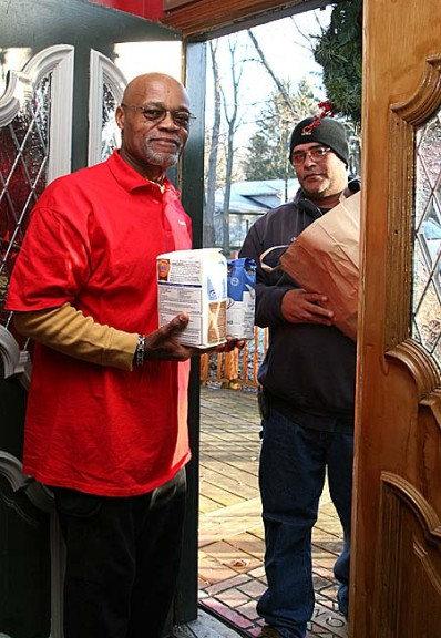 Last week Village Council member Gerry Simms received holiday baking staples from Village employee Chris Hamilton as part of the legacy of ex-slave Wheeling Gaunt, which mandates that the Village provide flour and sugar to all local widows and widowers. (Photo by Suzanne Szempruch)