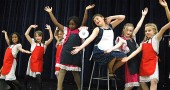 "The canteen girls sing ""Corns for My Country"" in Mills Lawn's all-school musical, The Albert Brown Show, which opens on Friday. Pictured are, from left, Zoe Williams, Lily Rainey, Maggie Knopp, Ateerys Wagner, Julia Hoff, Anastasia Cooper and Sophia Bottelier. Not pictured are Shaylee Smith and Ashley Shaffer. (Photo by Megan Bachman)"