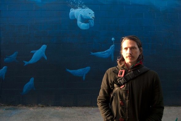 Pierre Nagley stands in front of his mural in Keith's Alley