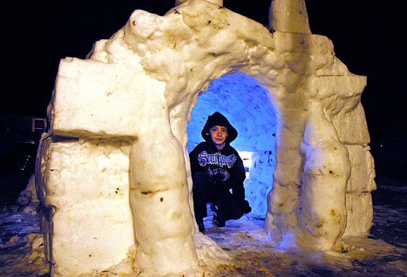 Cody Back, shown above, took advantage of the last two weeks of snow and cold to construct an igloo at his Robinwood Drive home. Helped by his parents, Scott Stolsenberg and Bettina Solas, Cody used recyling bins to mold the snow for the igloo, which features a lawn chair and lanterns inside. Warm temperatures in the next few days will test the igloo's durability. (photo by Lauren Heaton)