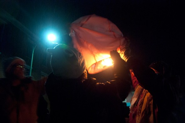 New Years revelers prepare to release a paper lantern into the night sky (photo by Aaron Zaremsky)