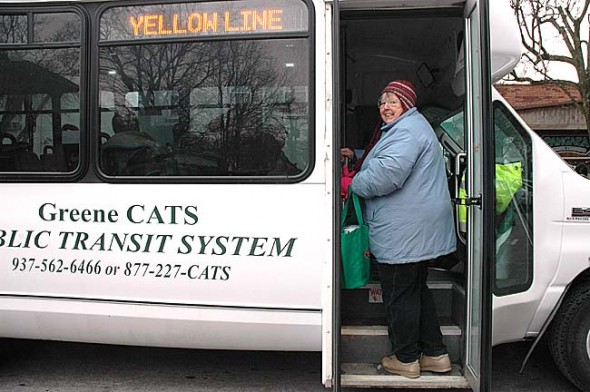 Barbara Mann, transportation coordinator for the Senior Center, hailed down a Greene Cats Yellow Line bus in front of Tom's Market on Monday, its first day of service to the village. The bus will come through town several times a day, taking riders to Xenia or Fairborn, where they can change to other buses that go to Dayton or Beavercreek. Bus schedules are available at the library, Senior Center and Village offices and on this site. (Photo by Diane Chiddister)