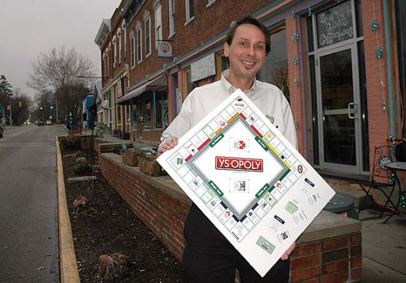 Brian Housh holds a copy of YS Opoly, a new Yellow Springs-based monopoly game, which is a fundraiser for the Yellow Springs Arts Council. Organizers are offering businesses and nonprofits who sponsor the game a featured place on the board. (Photo by Megan Bachman)