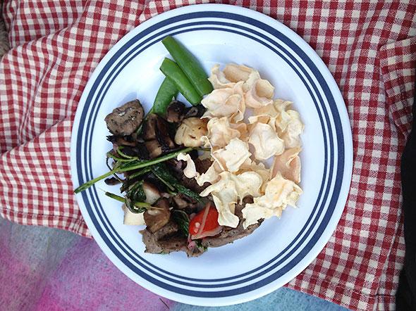 Picnic plate with lamb kabob, mushrooms, and sweet potato chips