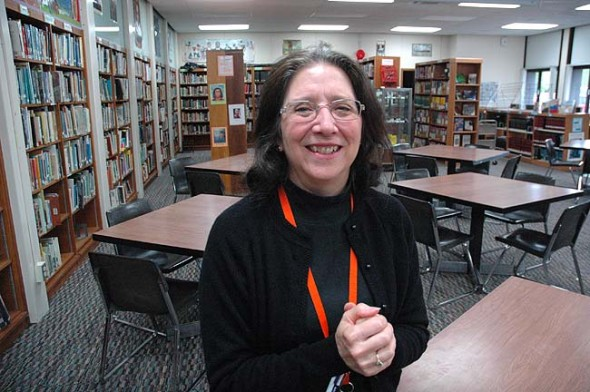 Yellow Springs School's librarian Mary Ann Christopher retires this month after 25 years with the district. Christopher, who lives in Beavercreek, spent 16 years in the library. Here she stands amongst the stacks she helped cultivate at the YSHS library. (Photo by Megan Bachman)