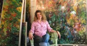 Jennifer Rosengarten sits in front of her many large, colorful oil paintings which are on display at the Dayton Visual Arts Center. (photo by Diane Chiddister)
