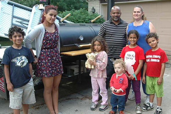 Everyone in the Williams family, including, from left, Judah, Shekinah, Hadassah, Tomaz, Agustus, Zoe, Margaret, Elijah and Jenesis (not pictured), will contribute to this weekend's launch of Pig Wings Barbeque, a food cart business that will be stationed at Village BP Wednesdays through Sundays. (Photo by Lauren Heaton)