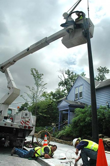 Village electric crew members Dan Mayenschein (in bucket), Chris Hamilton and Jane Hamilton installed one of the three new streetlights on Xenia Avenue last week. They will install 18 new lights on Dayton Street soon.