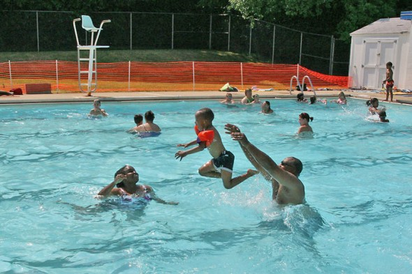 Gaunt Park pool reopened last Friday after having been closed for a week due to the overapplication of an herbicide on the pool lawn. Village Council had the lawn cordoned off, and will decide at its July 1 meeting when to remove the fence. Shown above are swimmers enjoying the water last Sunday afternoon. (Photo by Suzanne Szempruch)