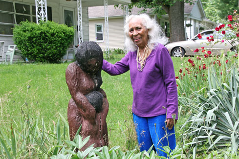 Maxine Jones posed with her wood carving in her garden on Livermore Street. It was given to her over 25 years ago and she's always liked it because it reminds her of herself and her son. (photos by Suzanne Szempruch)