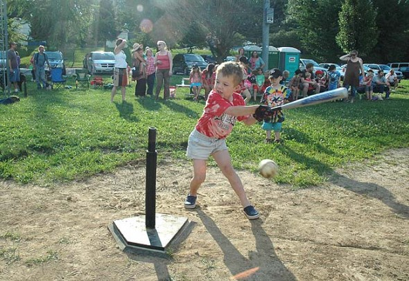 Swing, swing, swing!  Perry League t-ball kids and parents have been carrying on in honor of Coach Jimmy since the accident two weeks ago when Jimmy Chesire sustained a serious head injury after a fall at Ellis Park. On a recent Friday night Quentin Branlat, above, gave his swing all he had, and sent the ball flying. Chesire continues to improve at the Kettering Medical Center, and will soon be moved out of Intensive Care, according to Facebook updates from his wife, Robin Suits. See a report on last Friday's t-ball outing by parent Geneva Gano on page 10. (Photo by Matt Minde)