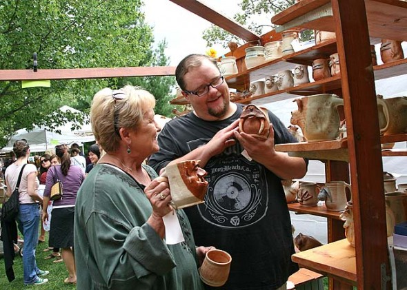 West Freeman browsed the handcrafted pottery of Dick Overman of Cincinnati with his mother, Barbara, at last year's Art on the Lawn. This year's art fair, 10 a.m. to 5 p.m. on Saturday, Aug. 10, is Village Artisan's 30th annual. (Photo by Suzanne Szempruch)