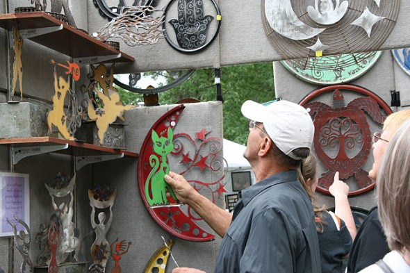 At last year's Art on the Lawn, a customer browses the eco-spiritual art of Kotah Moon, the winner of the 2012 Best in Show award. Kotah Moon will return for this year's Art on the Lawn on Saturday, Aug. 10. (Photo by Suzanne Ehalt)