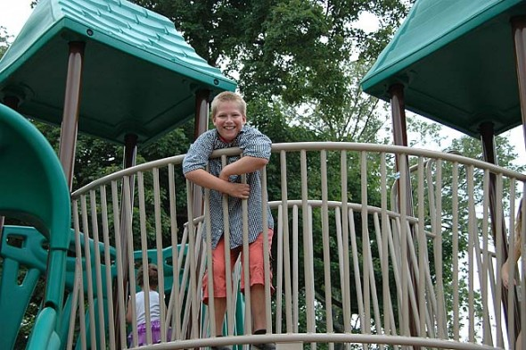 Soon-to-be-third-grader Sven Meister stands proudly atop the new Mills Lawn School climber. The climber was officially unveiled Thursday, Aug. 8, in the afternoon. Families and friends were encouraged to come and play and picnic. (Photos by Matt Minde)