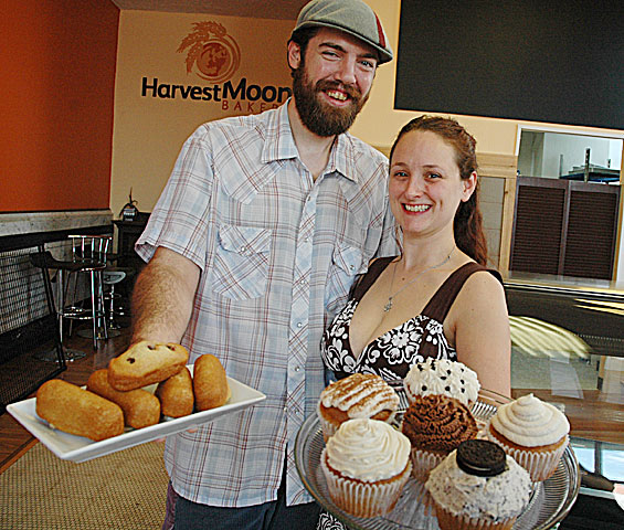 Chris and Andrea Hutson will open Harvest Moon Bakery in downtown Xenia next week. The bakery will sell exclusively-vegan baked goods like cakes, muffins, cookies and more. The Yellow Springs couple has operated a commercial wholesale vegan bakery from their Xenia Avenue apartment for the last six years. Here Chris shows off his  chocolate, vanilla and raspberry twinkys, and Andrea displays various cupcakes, including tiramisu, chocolate, lemon, cookies n' cream, strawberry jam-filled and vanilla with chocolate chips. (Photo by Megan Bachman)