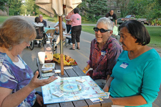 From left, Moya Shea, Karen McKee and Judy Skillings met over cold drinks and YSopoly on Saturday at a West Limestone Street block party, one of 11 Yellow Springs block gatherings over the Aug. 18 weekend. (Photos by Anisa Kline)