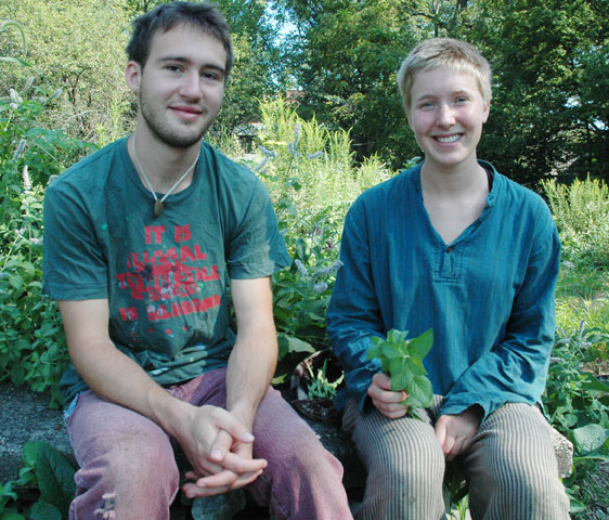 Antioch students Gabe Amrhein and Norah Mermis are two of the organizers of an upcoming skill-share workshop from 10 a.m. to 4 p.m. on Saturday, Aug. 24, in McGregor Hall on the Antioch campus. The event features 16 sessions on everything from zine-making to fermentation and is free and open to the public. Here Mermis and Amrhein gather spearmint in preparation for Mermis' session on making herbal tea remedies. (Photo by Megan Bachman)