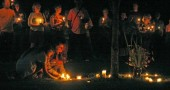 Villagers laid their candles under a tree at Mills Lawn in memory of Paul E. Schenck.