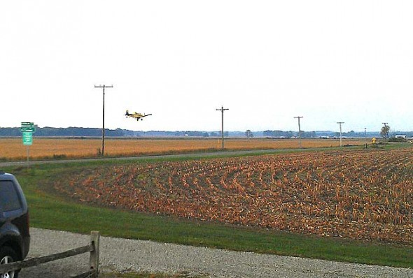 Local farmer Jim Clem will soon begin aerial seeding on his fields north of the village. Clem is spreading the word that the aircraft won't be spraying pesticides but seeding cover crops to help enhance the soil. Here an aircraft seeds an area field. (Photo courtesy of Integrated AG Services)