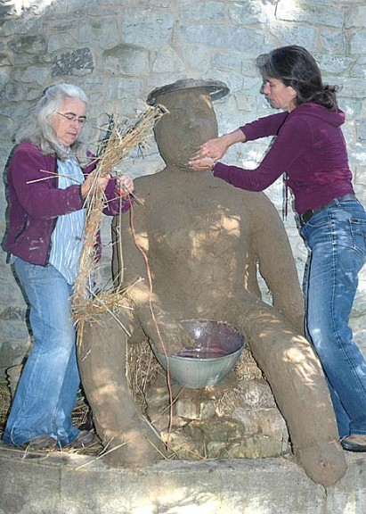 Beth Holyoke and Käthi Seidl add the finishing touch to their clay woman that sits outside the Glen Helen Building where their artwork is on display. The 'Clay!' exhibit continues through November 3. (Photo by Diane Chiddister)