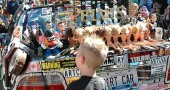 A small Street Fair goer stares down a Mr. Potatohead affixed on the back of the art car. (Photo by Anisa Kline)