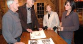The Hammond family plans to model their Mills Park Hotel on the Barr property after the 1870 Mills House (see below). Pictured from left are Jim Hammond, Chamber of Commerce representative Roger Reynolds, and Libby and Katie Hammond, talking over the plans at the Grinnell Mill. (Photo by Lauren Heaton)
