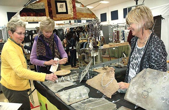 Thirty-one artists from Ohio, Kentucky and Indiana sold their wares, including, at top right, jewelry artist Janet Webb from Marion, Ind., who is showing her sterling silver pieces to Janet Heater, left, of Springfield and Phyllis Sloan of Mt. Vernon. The event donates a portion of ticket sales to the schools and the police coat fund; each organization received $392 from the event. (Photo by Diane Chiddister)