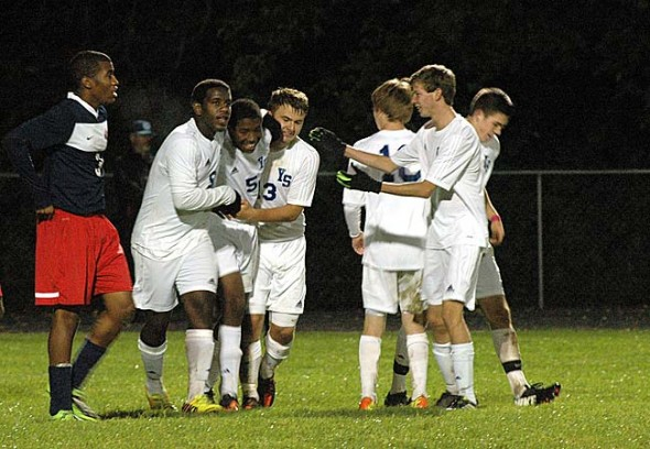 Players on the YSHS varsity soccer team celebrate a goal during the team's 6–2 defeat of Miami Valley in the district tournament in October. The team ultimately fell in the district finals but ended the season as the outright MBC champs. (Photo by Lauren Heaton)