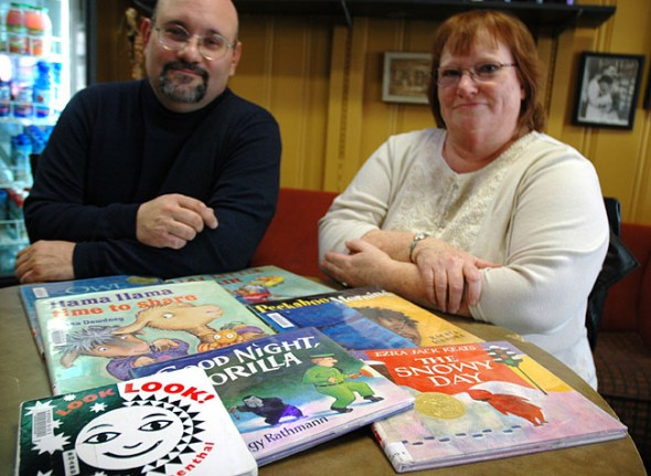 Greene County Library Director Karl Colón and Youth Services Coordinator Kay Webster helped to launch the Dolly Parton Imagination Library locally last month. All children under five can sign up to receive a free book mailed to their home each month as part of the program. Some of the books being sent are in the foreground. (Photo by Megan Bachman)