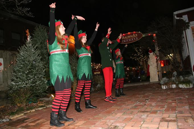 Outside Asanda Imports on Thanksgiving weekend, Santa's Elves performed as a crowd of adults and children gathered for the annual tree lighting. When the elves are not performing or helping Santa, they go by the names Morgan Wheeler, Emory Schweitzer, Dylan Koepp, and Layne Burner and are students at Tecumseh High School. They will perform again when Santa comes to the Glen Helen building on Saturday, Dec. 14. (Photo by Suzanne Szempruch)