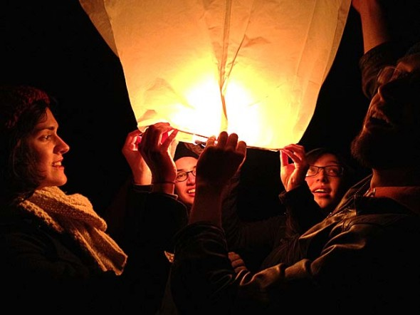 "In March about 40 Antioch College students launched their ""intentions""— inscriptions of their hopes and wishes on paper hot air balloons — before leaving for their first co-op term the following day. Pictured from left are Elaine Bell, Kijin Higashibaba, Cleo Van der Veen and Gabe Amrhein, about to release their balloon. (Photo by Matt Minde)"