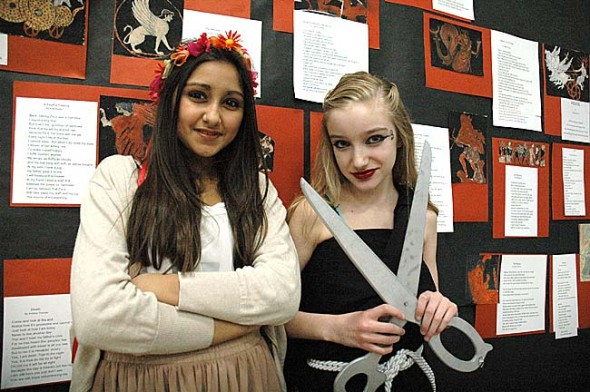 Above, Ischel Heredia, left, dressed as Persephone, and Anastasia Cooper, dressed as one of the Fates, stand in front of the seventh-grade's Ancient Greece project. (Photo by Matt Minde