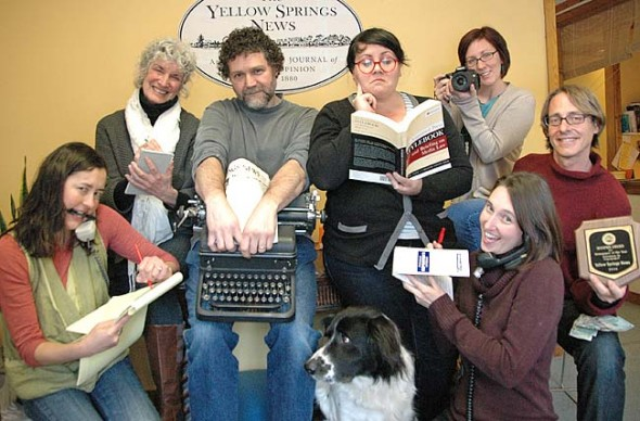 The Yellow Springs News recently won the top prize in its size category at the annual convention of the Ohio Newspaper Association. Shown above are fulltime staff members, from bottom left clockwise: Lauren Heaton, Diane Chiddister, Matt Minde, Lauren Shows, Suzanne Szwmpruch, Bob Hasek, Megan Bachman and Tucker the Newshound.